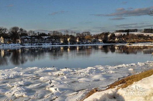 The open river but for ice near the shores.